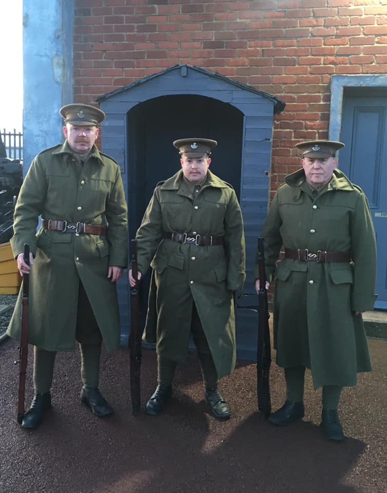 Three members of the Durham Pals in First World War uniform stand in front of the Heugh Battery.